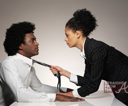 Businesswoman pulling necktie of a businessman at office desk