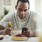 black_man_text_messaging_and_eating_breakfast_BLD080951